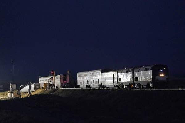 Engines and cars from an Amtrak train that derailed a day earlier are shown illuminated by floodlights, late Sunday, Sept. 26, 2021, near Joplin, Mont. (AP Photo/Ted S. Warren)