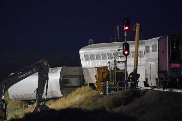 Cars from an Amtrak train that derailed the day before are shown illuminated by floodlights, late Sunday, Sept. 26, 2021, as they rest near a train signal near Joplin, Mont. (AP Photo/Ted S. Warren)