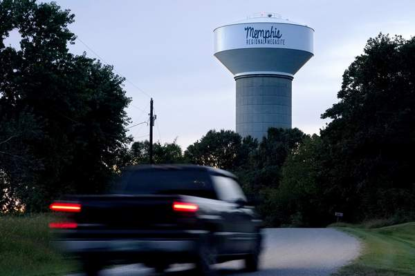 A truck drives down a rural road near a water tower marking the location of the Memphis Regional Megasite on Sept. 24, 2021, in Stanton, Tenn. Ford Motor Co. and SK Innovation of South Korea plan to build three new electric-vehicle battery factories and an auto assembly plant by 2025 in Tennessee and Kentucky. (AP Photo/Mark Humphrey)