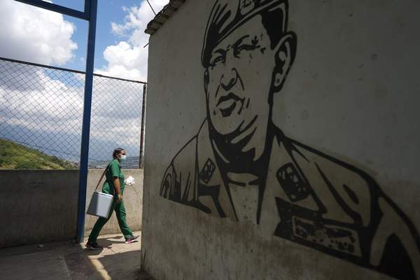 Nurse Genny Zorrilla walks with a cooler containing Sinopharm COVID-19 vaccines past a mural of late president Hugo Chavez, during house to house vaccinations in the popular neighborhood of El Valle in Caracas, Venezuela, Monday, Sept. 27, 2021. (AP Photo/Ariana Cubillos)