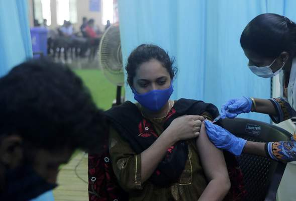 A health worker inoculates a school teacher Iram Mohammed Salim Khan with the vaccine for COVID-19 during a special drive for teachers and students in Mumbai, India, Tuesday, Sept. 28, 2021. (AP Photo/Rajanish kakade)