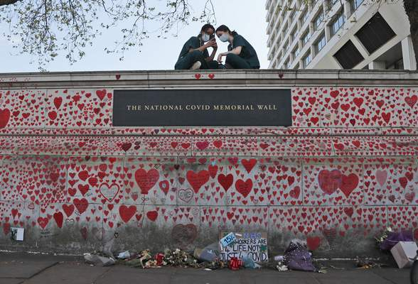 FILE - In this Tuesday, April 27, 2021 file photo, nurses from the nearby St Thomas' hospital sit atop the National Covid Memorial Wall in London. (AP Photo/Frank Augstein, file)