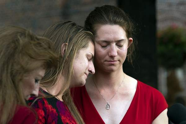 Summerleigh Winters Geimer, center, and her sister Montana Winters Geimer, right, daughters of Wendi Winters, a community beat reporter who was killed in the Capital Gazette newsroom shooting, react during a news conference following the sentencing verdict of Jarrod W. Ramos, Tuesday, Sept. 28, 2021, in Annapolis, Md. (AP Photo/Jose Luis Magana)