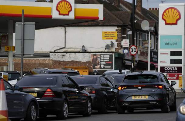 Drivers queue for fuel at a petrol station in London, Tuesday, Sept. 28, 2021. (AP Photo/Frank Augstein)