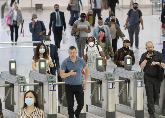People commute through the World Trade Center, Friday, July 9, 2021, in New York. Businesses that have announced vaccine mandates say some workers who had been on the fence have since gotten inoculated against COVID-19. (AP Photo/Mark Lennihan)