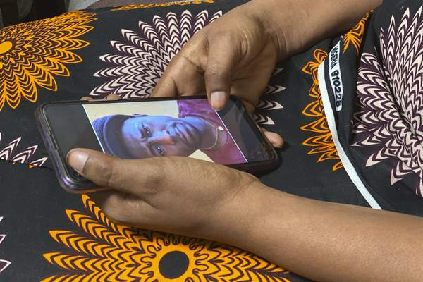 FILE - In this Friday, March 5, 2021 file photo, Anifa holds her phone displaying a photo of former World Health Organization doctor Boubacar Diallo of Canada, during an interview in the eastern Congo town of Goma. (AP Photo/Kudra Maliro, File)