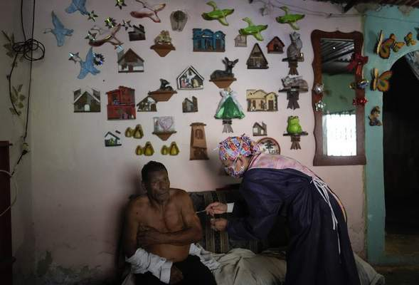 Nurse Rosaura Rodriguez inoculates a man with a dose of the Sinopharm COVID-19 vaccine during house to house vaccinations in the popular neighborhood of El Valle in Caracas, Venezuela, Monday, Sept. 27, 2021. (AP Photo/Ariana Cubillos)