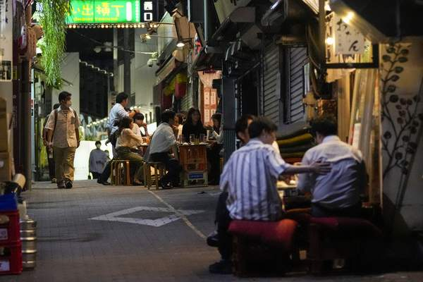People gather at bars that are open and serving alcohol on an ally filled with bars and restaurants despite Tokyo government has requested businesses not to serve alcohol under the state of emergency Wednesday, Sept. 22, 2021, in Tokyo. (AP Photo/Kiichiro Sato)