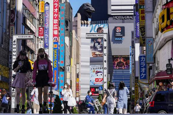 FILE - In this Sept. 20, 2021, file photo, people wearing face masks to help protect against COVID-19 walk past a crossing in Shinjuku, an entertainment district of Tokyo. (AP Photo/Kiichiro Sato, File)