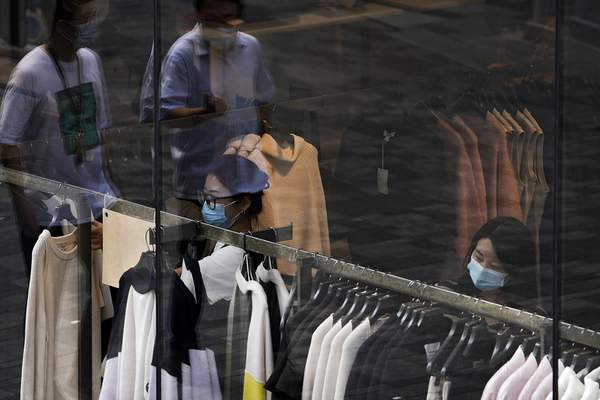 People wearing face masks to help protect from the coronavirus walk through a capital popular shopping mall as masked women selecting clothes at a fashion boutique in Beijing, Tuesday, Sept. 28, 2021. (AP Photo/Andy Wong)