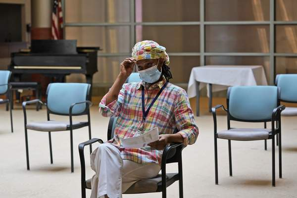 Shyrel Ritter, a certified nursing assistant at the Hebrew Home at Riverdale, waits to receive her COVID-19 booster shot at her workplace in New York, Monday, Sept. 27, 2021. (AP Photo/Seth Wenig)