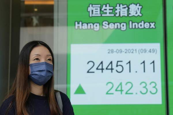 A woman wearing a face mask walks past a bank's electronic board showing the Hong Kong share index in Hong Kong, Tuesday, Sept. 28, 2021. (AP Photo/Kin Cheung)