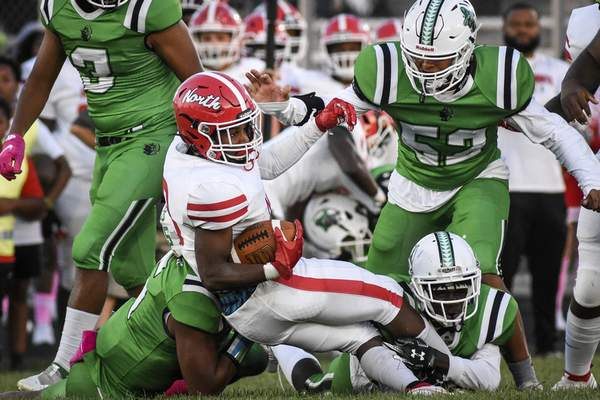 Mike Moore | The Journal Gazette North Side running back Jontae Lambert is brought down by South Side defenders on Friday night.