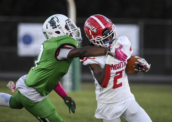 Mike Moore | The Journal Gazette North Side's Bravon Basset tries to break a tackle during Friday's game against South Side.