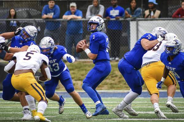 Mike Moore | The Journal Gazette University of Saint Francis quarterback Heath Simmons looks for a receiver in the second quarter against Siena Heights on Saturday.