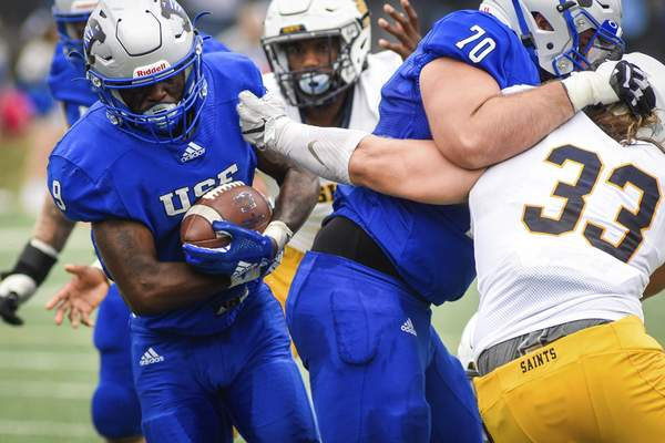 Mike Moore | The Journal Gazette University of Saint Francis running back Cameron Peterson carries the ball for a gain on Saturday in the second quarter against Siena Heights at Bishop D'Arcy Stadium.