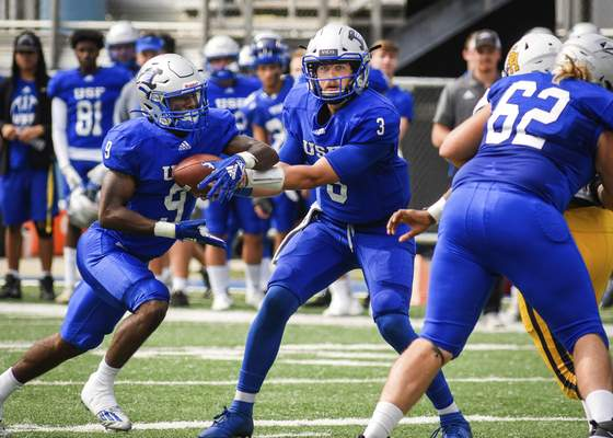 Mike Moore | The Journal Gazette University of Saint Francis quarterback Heath Simmons hands the ball off to running back Cameron Peterson in the first quarter against Siena Heights on Saturday.
