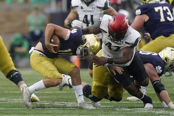 Associated Press photos Notre Dame quarterback Drew Pyne is sacked by Cincinnati's Malik Vann during the second half of Saturday's game in South Bend. Pyne replaced Jack Coan after the Irish fell behind 17-0 at halftime.