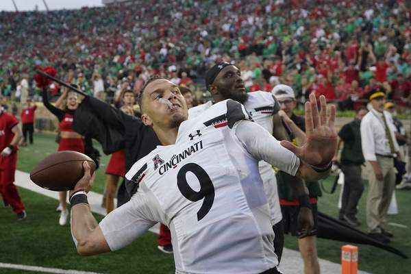 Cincinnati quarterback Desmond Ridder throws a football into the standsafter Saturday's win, which snapped Notre Dame's home winning streak at 26 games.
