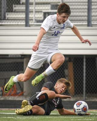 Mike Moore | The Journal Gazette Homestead midfielder Nicholas Gallagher leaps over Huntington North forward Gabriolle Castillo as he slides for the ball in the first half of Wednesday's 3A Soccer Sectional at New Haven High School.