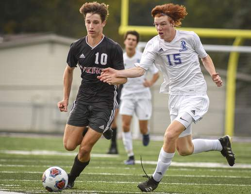 Mike Moore | The Journal Gazette Huntington North's Aric Hosler and Homestead's Cameron Jarrett race for the ball during Wednesday's sectional semifinals match at New Haven.