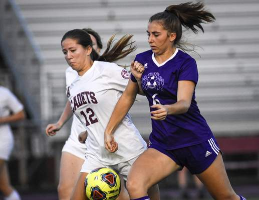 Mike Moore   The Journal Gazette Cadets' defense Campbell Twomey, left and Lions' midfielder Ella Graves clash for the ball Saturday in the first half at Zollner Stadium.