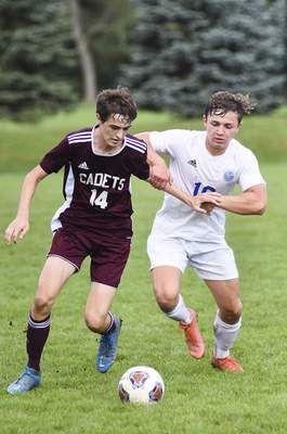 Katie Fyfe | The Journal Gazette Concordia sophomore Christopher Hawk and Canterbury senior Zachary Hobbs run to the ball during the first half of the Boys Soccer Sectional Final at Canterbury High School on Saturday.