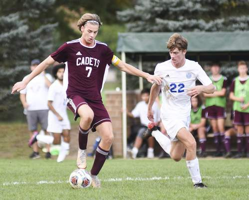 Katie Fyfe | The Journal Gazette  Concordia Lutheran senior Elijah Macke kicks the ball down the field with Canterbuy junior Collin Campbell close behind during the first half at Canterbury High School on Saturday.
