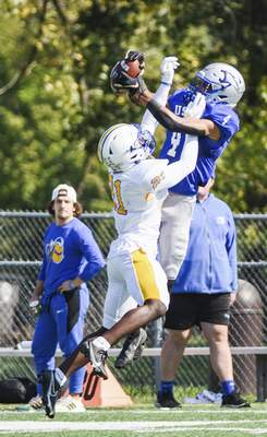 Katie Fyfe | The Journal Gazette  USF wide reciever D'Andre Miles and Madonna cornerback Julius Adams jump for the ball during the first quarter at Bishop D'Arcy Stadium on Saturday.