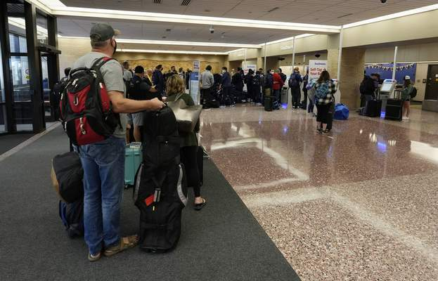 Passengers queue up at the ticketing counter for Southwest Airlines flights in Eppley Airfield Sunday, Oct. 10, 2021, in Omaha, Neb. (AP Photo/David Zalubowski)
