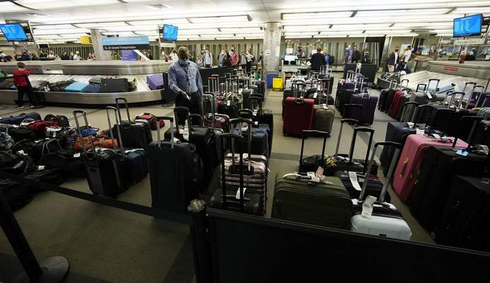 Unclaimed baggages wells up between carousels for passengers arriving on Southwest Airlines flights at Denver International Airport late Sunday, Oct. 10, 2021, in Denver. (AP Photo/David Zalubowski)