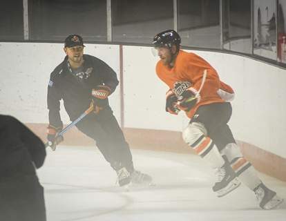 Photos by Mike Moore | The Journal Gazette Komets head coach Ben Boudreau, left, skates with his team Monday during the first day of training camp.