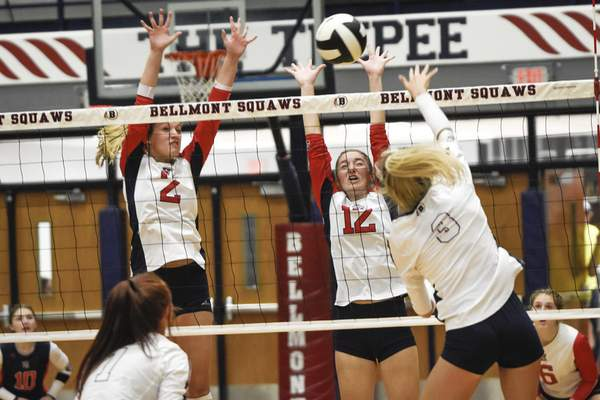 Mike Moore | The Journal Gazette Heritage sophomore Lainey Simmons, left, and junior Alyson Stinson, center, go up for the block as Bellmont senior Avery Ball spikes the ball in Decatur on Tuesday.
