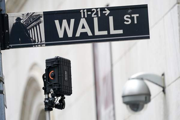 FILE - A Wall Street sign is seen next to surveillance equipment outside the New York Stock Exchange, Tuesday, Oct. 5, 2021, in New York. (AP Photo/Mary Altaffer)