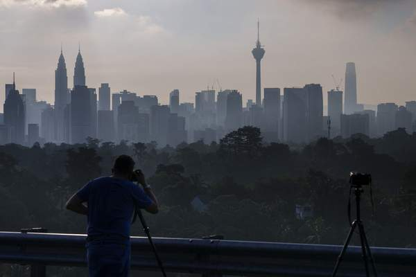 A photographer takes pictures of morning city view of Kuala Lumpur, Malaysia, Monday, Oct. 11, 2021. (AP Photo/Vincent Thian)