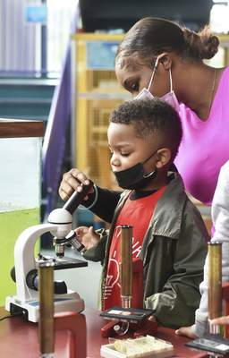 Katie Fyfe | The Journal Gazette  Quantae Jackson, 3, with Little Thinkers of Early Learning looks through a microscope during Today's Observers Tomorrow's Scientists I Spy session at Science Central on Tuesday.