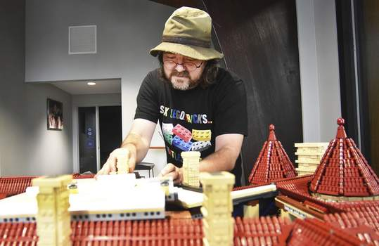 """Photos by Katie Fyfe   The Journal Gazette  Jason Pyett puts the final pieces on his 63,807-piece Lego replica of the Brookside Mansion at the University of Saint Francis Welcome Center on Tuesday. """"The travel was a story unto itself,"""" said Pyett, who is from Canada."""