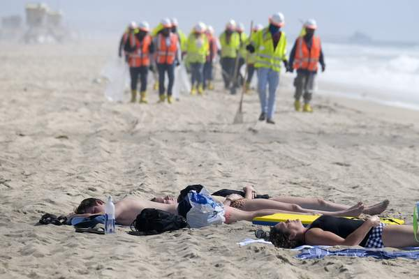 Associated Press Beachgoers rest as workers continue to clean the contaminated beach in Huntington Beach, Calif.