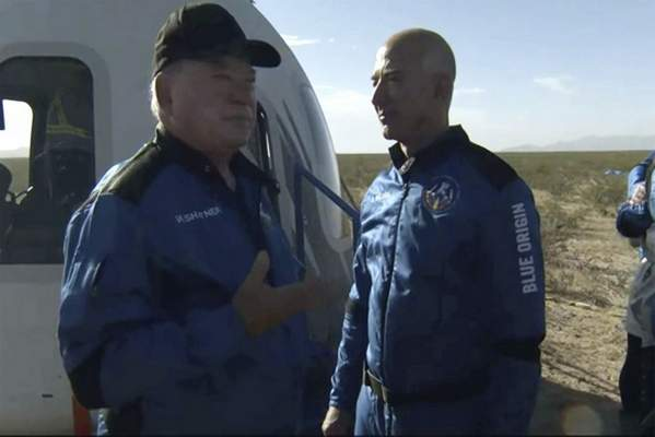 In this image provided by Blue Origin, William Shatner talks with Jeff Bezos about his experience after exiting the Blue Origin capsule near Van Horn, Texas, Wednesday, Oct. 13, 2021. (Blue Origin via AP)