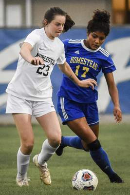 Mike Moore | The Journal Gazette Noblesville forward Meredith Tippner, left, and Homestead defence Sophia White spar for the ball on Wednesday in the first round of the girls soccer regionals at Homestead High School.