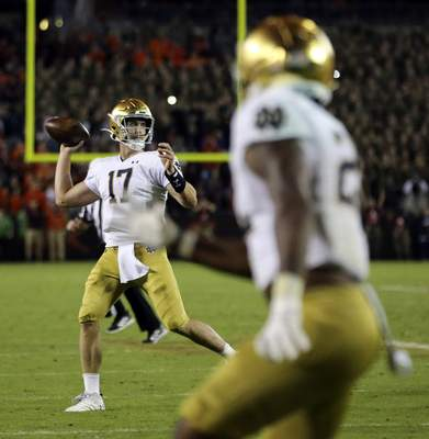 Notre Dame quarterback Jack Coan (17) throws a two-point conversion pass during the second half of an NCAA college football game against Virginia Tech in Blacksburg, Va., Saturday, Oct. 9, 2021. (AP Photo/Matt Gentry)