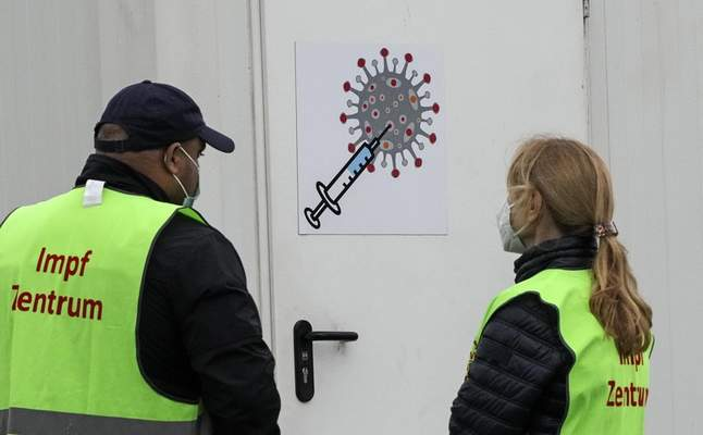Helpers stand in front of COVID-19 vaccination center in a container near the main train station in Duisburg, Germany, Tuesday, Oct. 12, 2021. (AP Photo/Martin Meissner)