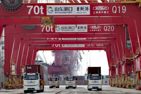Container trucks pass through a new automated container port in Rizhao in eastern China's Shandong province on Oct. 9, 2021. (Chinatopix via AP)