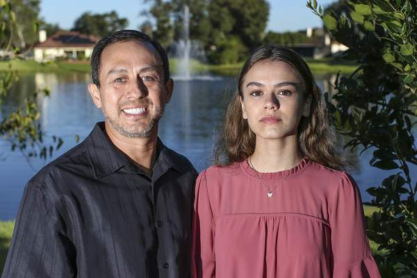 Portrait of Mitch Arbelaez and his daughter Jayden in Jacksonville, Fla., Wednesday, Oct. 13, 2021. (AP Photo/Gary McCullough)