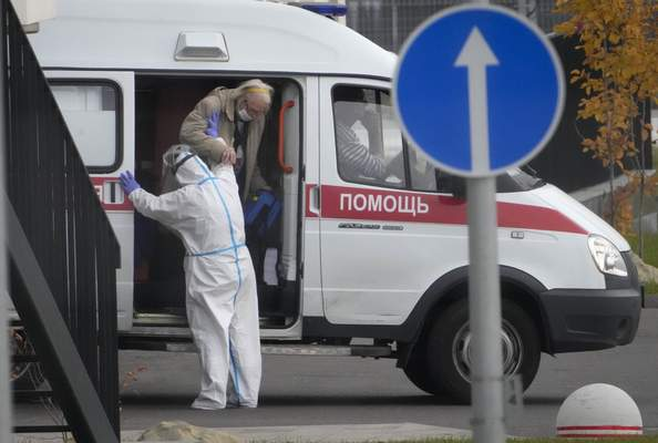 A medical worker helps a patient suspected of having coronavirus to leave an ambulance at a hospital in Kommunarka, outside Moscow, Russia, Tuesday, Oct. 12, 2021. (AP Photo/Alexander Zemlianichenko)