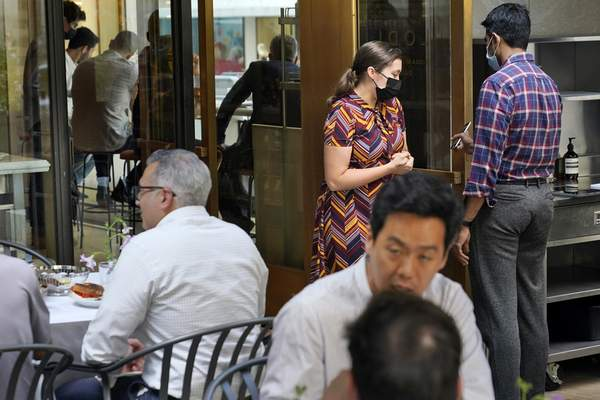 FILE: In this Sept. 13, 2021 file photo. Maitre d' Susanne McDonald, center right, checks a guest's proof of vaccination at a restaurant in midtown Manhattan, in New York. (AP Photo/Seth Wenig, File)