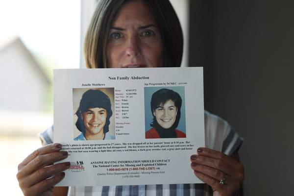 FILE - In this Aug. 12, 2019, file photo, Jennifer Mogensen holds a poster of her adopted sister, Jonelle Matthews, who went missing and whose remains were found recently in Greeley, Colo. (AP Photo/David Zalubowski, File)