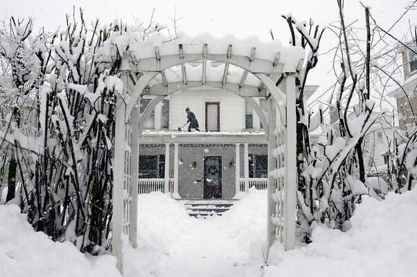 FILE - Amber Cox shovels snow from the porch roof at her home in Auburn, Maine, on March 8, 2018. (Daryn Slover/Sun Journal via AP)