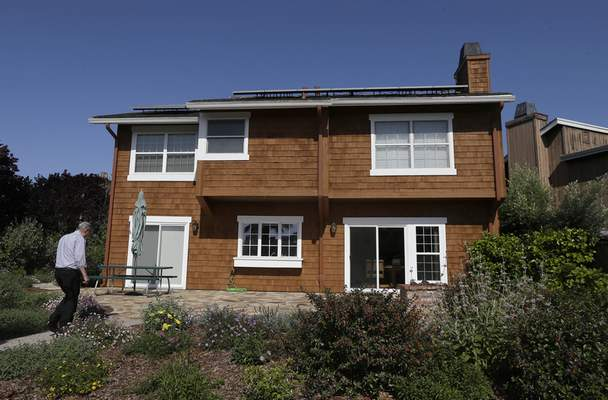 FILE - David Cunningham walks toward his solar panel-topped home, on April 20, 2015, in Foster City, Calif. (AP Photo/Jeff Chiu, File)
