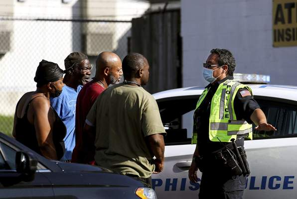 Memphis Police Department officers talk to nearby residents after a deadly shooting at a nearby post office Tuesday, Oct. 12, 2021 in the Orange Mound neighborhood of Memphis, Tenn. (Patrick Lantrip/Daily Memphian via AP)